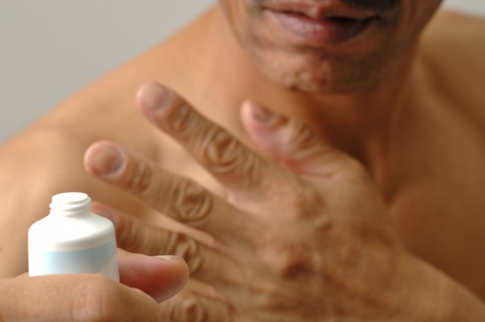 身体にクリームを塗る男性