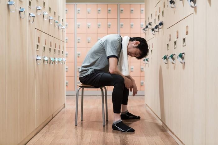 トレーニングジムの更衣室でイスに座る男性