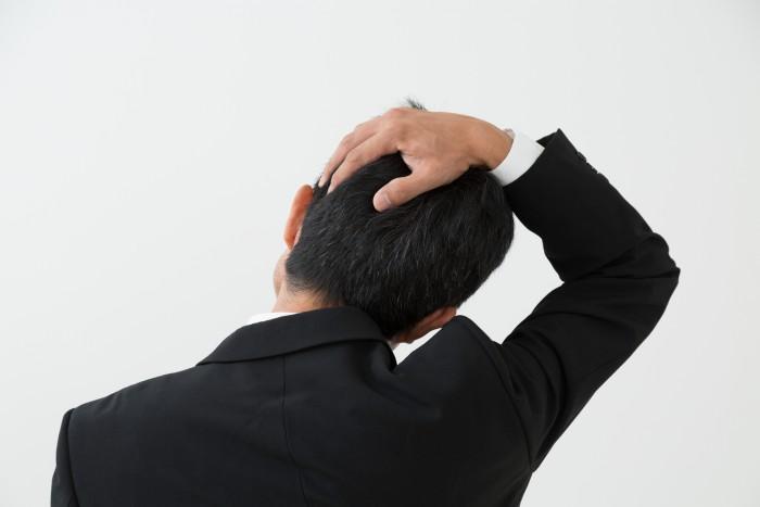 首のこりに悩む男性