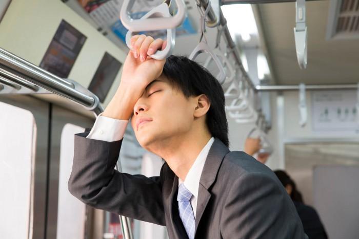 電車内で疲れ果てる男性